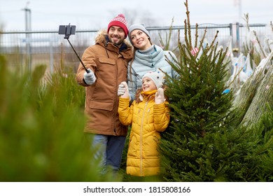 family, winter holidays and people concept - happy mother, father and little daughter buying christmas tree and taking picture with smartphone on selfie stick at street market