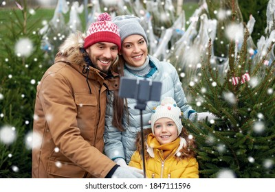 family, winter holidays and people concept - happy mother, father and little daughter buying christmas tree and taking picture with smartphone on selfie stick at street market over snow