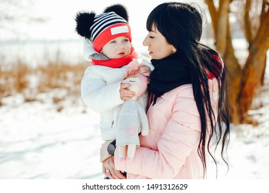 Family in a winter park. Elegant woman in a pink jacket. Mother with little daughter