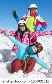 Vacances en ski d'hiver en famille. Trois filles avec des vêtements très colorés posant dans la neige fraîche et le ciel bleu, et levant les mains