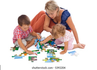 Family, woman and kids, playing with puzzle on the floor - isolated
