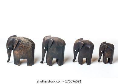Family of wooden elephants on white background