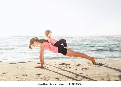 family workout - mother and daughter doing exercises on beach. Mom and child working out on seaside in the morning. Healthy lifestyle concept