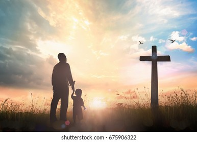 Family worship and holy bible story concept: Silhouette father and son looking for the cross on meadow autumn sunrise background.