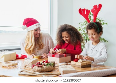 Family wrapping Christmas presents at the table
