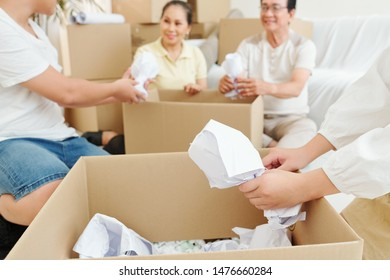 Family wrapping fragile tableware in paper when packing things in cardboard boxes