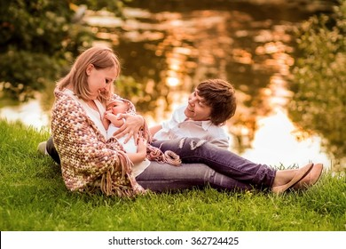 Family (young blond mother, dark-haired father and cute little baby boy) on the bank of a pond on the sunset. Image with selective focus and toning