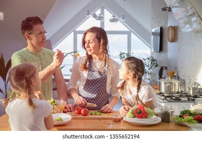 Family with young children cooking together in the kitchen at home