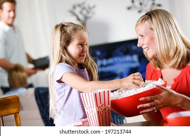 Family: Young Girl Helps Put Popcorn In Boxes