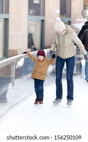 family of young mother and her son skating at winter
