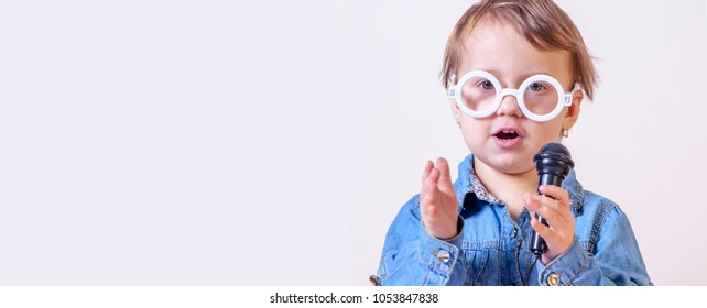 The famous actress. Humorous photo of cute child girl singing with a microphone (Happy childhood, teaching singing, music, child development concept)