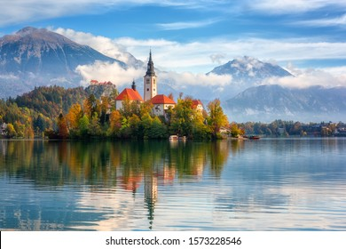 Famous alpine Bled lake (Blejsko jezero) in Slovenia, amazing autumn landscape. Scenic view of the lake, island with church, Bled castle, mountains and blue sky with clouds, outdoor travel background