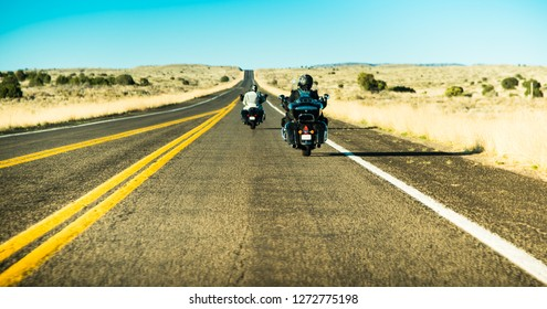 Famous American Historic road to the West - Route 66 with two silhouettes of motor bikers driving their motorcycles (heading North East) South California desert landscape background, U.S.A.