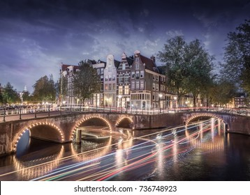 Famous Amsterdam canal with boat light trails