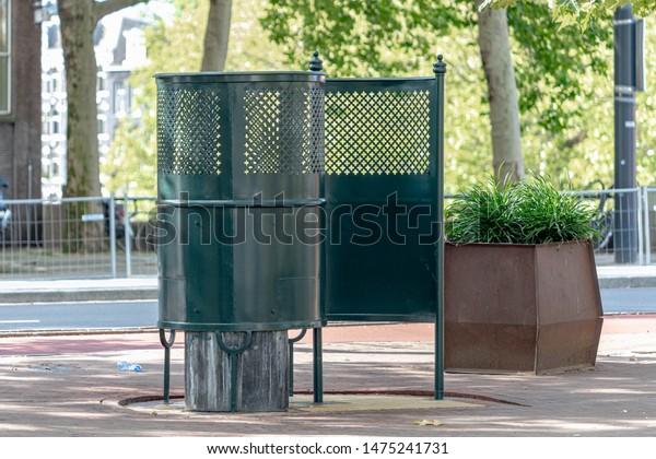 Famous Amsterdam open air pissoir (urinals) public toilet for men along street and canal, So-called De Krul in Dutch, Amsterdam, Netherlands.