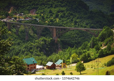 Famous arched concrete bridge in Montenegro - Dzhurdzhevicha Bridge on river Tara. River canyon. Nature and surrounding forests, mountains and space. Travel in summer to Europe by car and sightseeing.