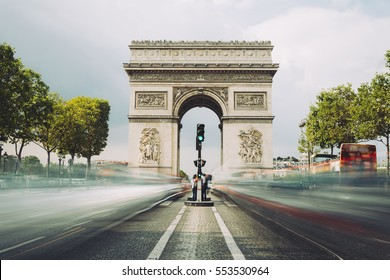 Famous avenue Champs-Elysees and the Triumphal Arch, symbol of the glory and historical heritage. Iconic touristic architectural landmark of Paris, France. Tourism and travel concept. Long exposure