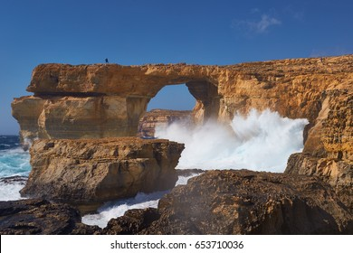 Famous Azure Window, Tieqa tad-Dwejra in Malta, now history due to collapse into the sea. Azure window with tourist silhouette on the top. Rocky coastline with big, stormy waves. Island Gozo, Malta