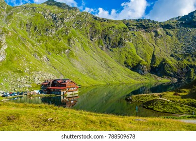 Famous Balea lake near Transfagarasan road in the Carpathian Mountains, Romania, Eastern Europe. Wood cabin, chalet, hotel, cottage. Glacial, green grass, rocks, summer vacation, landscape.
