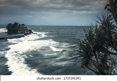 Célèbre temple de Bali Tanah lot en mer pendant la tempête avec de grandes vagues et un ciel sombre dramatique couvert