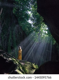 Famous Bali waterfall in the cave Tukad Cepung. Young girl in yellow long dress.