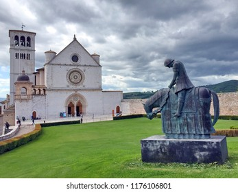 Famous Basilica of St. Francis of Assisi (Basilica Papale di San Francesco) with knight on horseback statue in cloudy day, Assisi, Umbria, Italy
