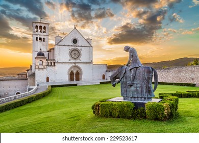 Famous Basilica of St. Francis of Assisi (Basilica Papale di San Francesco) with statue at sunset in Assisi, Umbria, Italy