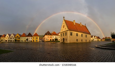 Famous baths Bardejov in Slovakia with old historical town square with preserved bourgeois houses with colorful facades listed in UNESCO world heritage with beautiful rainbow after storm and rain