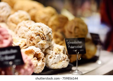 Famous Bavarian pastry - Snowball. Shopping on traditional Christmas market in Germany. Candy, pastry and gingerbread in confectionery. Choice of sweets in Xmas bakery.