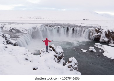 Famous and beautiful Icelandic waterfall Godafoss north iceland.Tourist photographer in red jacket standing at Godafoss powerful waterfall in winter.