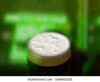 Famous black Irish stout with a frothy shamrock. Green St Patricks day background