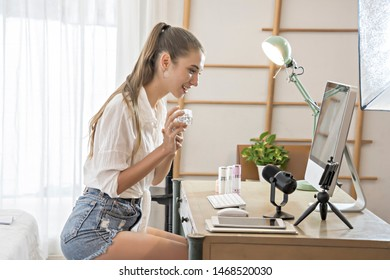 Famous blogger concept. Cheerful female blogger is showing cosmetics products while recording video with smartphone and giving advice for her beauty blog. Focus on digital camera cellphone.