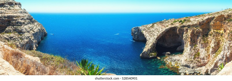 Famous Blue Grotto in Malta near Zurrieq on a calm sunny day. Horizontal panorama from 5 vertical frames.