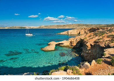 The famous blue lagoon in comino. A paradise with crystal clear azure-coloured water. View of the the coastline and the turquoise blue water with a luxury sailing boat. Vacation on the island of malta