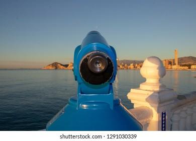 The famous blue telescope situated at the look out point Balcón del Mediterráneo & Mirador del Castell in Benidorm Alicante in Spain with Mirador de la Isla de Benidorm in the background.