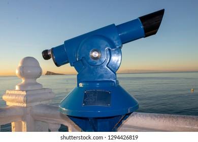 The famous blue telescope situated at the look out point Balcón del Mediterráneo & Mirador del Castell in Benidorm Alicante in Spain with Mirador de la Isla de Benidorm in the background at sunrise.