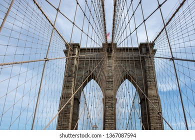 The famous Brooklyn Bridge Bridge located in New York City in the United States of America showing the suspension wired and the USA flag at the top of the column on a part cloudy day with blue Skys.