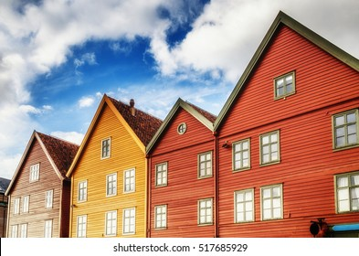 Famous Bryggen street in Bergen Norway - architecture background. Color houses builings at blue sky with clouds background and bright windows mirorred sun  light in sunset time.