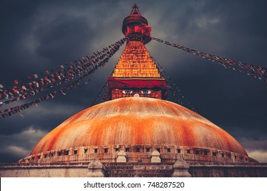 The famous Buddhist stupa at Boudanath in Kathmandu valley, Nepal. Wisdom eyes. Dranatic dark cloudy sky in the background. Travel, holidays, place to visit. Vintage retro toning filter