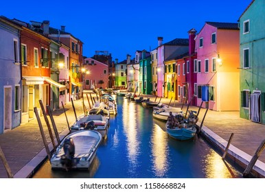 Famous Burano island at night, Venice, Venetian Lagoon, Italy. Old city colorful houses along the small beautiful canal with boats against dusk blue sky. Wellknown tourist italian landmark.
