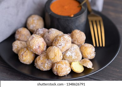 Famous Canary Islands dish, Papas Arrugadas (wrinkly potatoes with salt) and Mojo picon (red  spicy sauce) on wood table in local restaurant.