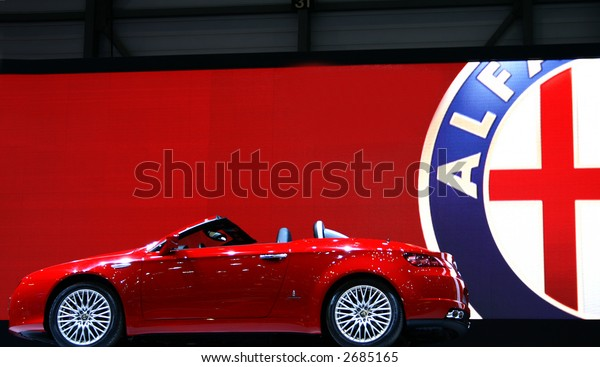 Famous Car on Display with Car Logo Background.