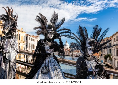 Famous Carnival masks on bridge against Grand Canal in Venice, Italy