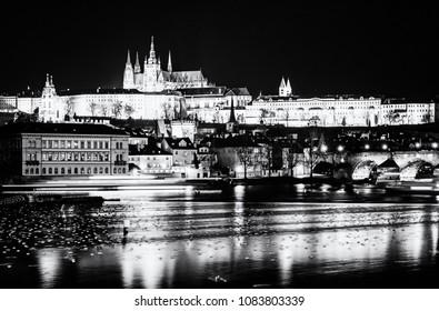 Famous castle and Charles bridge mirroring in Vltava river, Prague, Czech republic. Night scene. Travel destination. Architectural scene. Black and white photo.