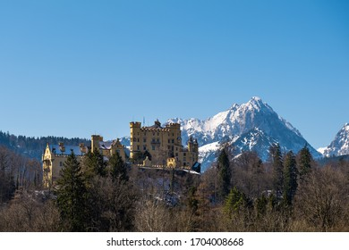 Famous castle Hohenschwangau during springtime with the snowcapped mountain Gehrenspitze in the background and blue sky
