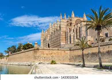 Famous Cathedral of Santa Maria under blues sky as seen from Parc de la Mar in Palma de Mallorca, Spain.