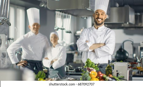 Famous Chef of a Big Restaurant Crosses Arms and Smiles in a Modern Kitchen. His Staff in Smiling in the Background.