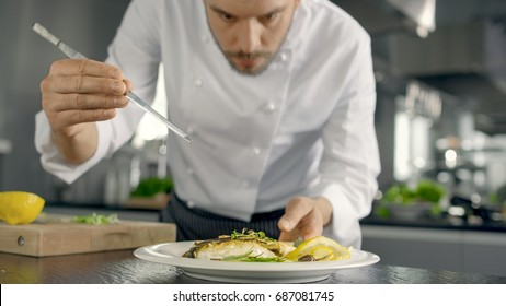 Famous Chef Decorates His Special Fish Dish with Some Greens. He Works in a Modern Kitchen.