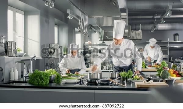 Der berühmte Küchenchef arbeitet mit seiner Hilfe in einer großen Küche. Die Küche ist voll von Essen, Gemüse und Kochgeschirr.