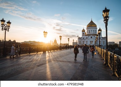 Famous christian landmark in Russia - Christ the Savior cathedral at sunset. Golden sunset lights on a bridge in Moscow, outdoor autumn in Russia. Christ the Savior cathedral, outdoor Moscow landscape